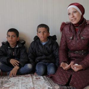 En mamma i röd slöja sitter på en säng i ett flyktingläger tillsammans med sina två små söner