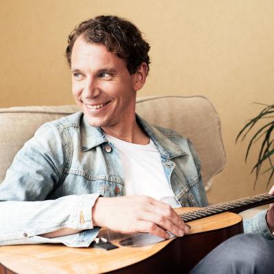 kirjailija Juha Itkonen istuu kitaran kanssa