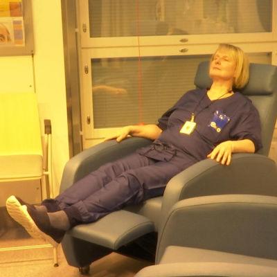 Nainen istuu tuolissa keltaisessa valossa keskussairaalan päivänvalohuoneessa