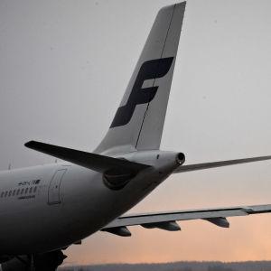 Finnairin lentokoneen peräosaa, kone seisoo kentällä.