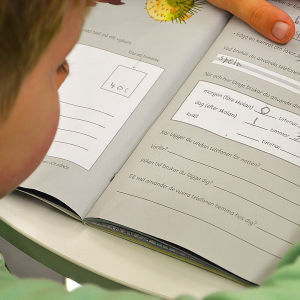 Ett barn gör uppgifter i en lärobok.