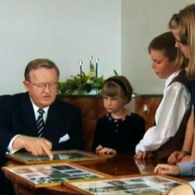 Martti Ahtisaari katgselee valokuvia Linnassa vierailevien lasten kanssa.