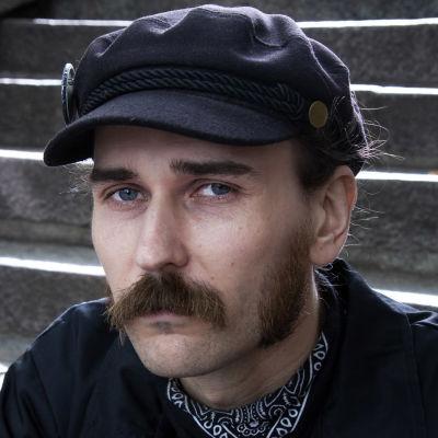 Ville Valavuo istuu portailla ja katsoo kulmien alta kohti kameraa.