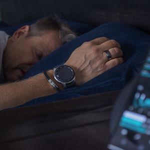 Mies nukkuu älykello ja -sormus kädessään.