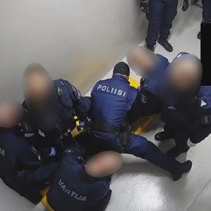 poliisit kiinniotetun miehen päällä