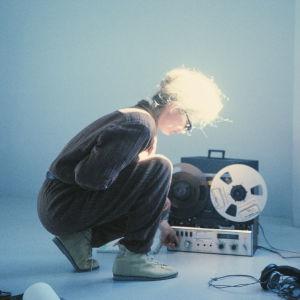 Vaaleatukkainen nainen on kyykistynyt kelanauhurin äärelle. Kuva dokumenttielokuvasta Sisters with Transistors.