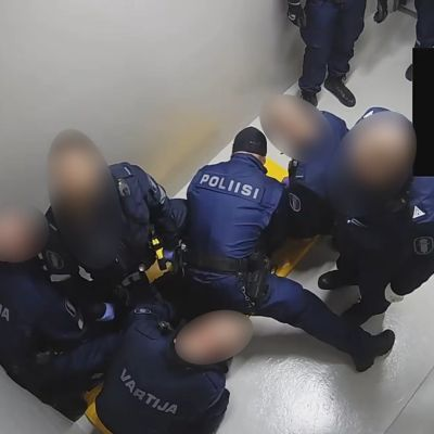 Två väktare och tre poliser står böjda ovanför en man som ligger på ett golv i polishäktet.