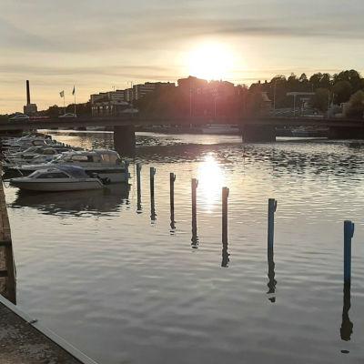 Solen går ner och speglas i Aura ås vatten i Åbo, där båtar ligger förtöjda i ån.