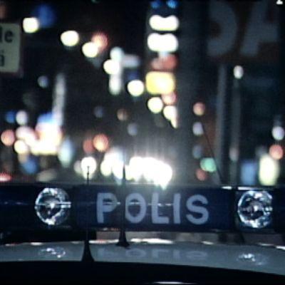 Polisbil i nattlig stad