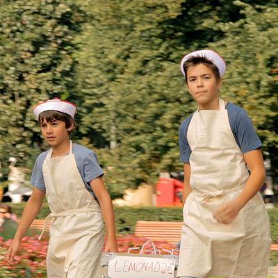 Två pojkar är utklädda till lemonadförsäljare.