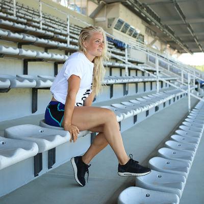 Valmentaja Oona Tolppanen istuu yleisiurheilukentän katsomossa.
