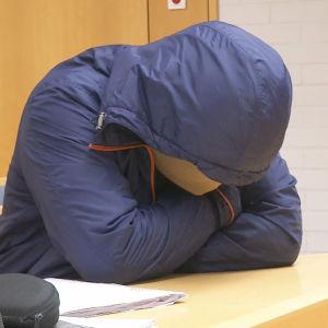 Syytetty kasvot peitettynä Oulun käräjäoikeudessa