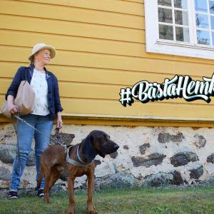 Hedda Kainz står lutad mot en gul gammal trävägg med hunden Buster. På väggen står det bästahemknuten.