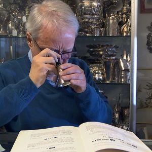 En man granskar en silverbägare med förstoringsglas.