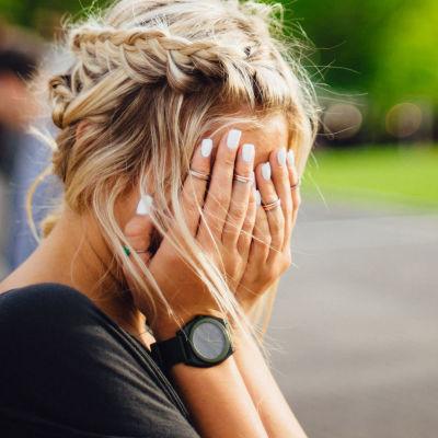 Nainen peittää kasvonsa käsillään.