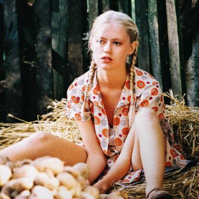 Tyttö istuu heinien ja perunakasan vieressä.