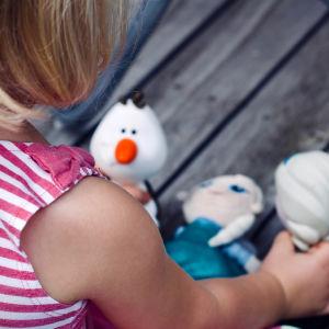 Tyttö leikkii nukeilla lattialla.