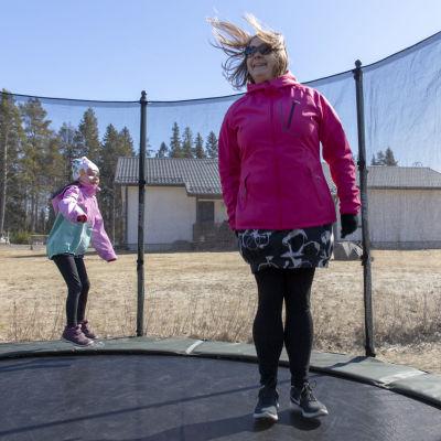äiti ja lapsi hyppivät trampoliinilla