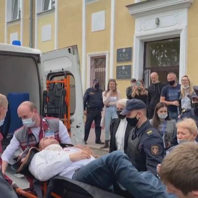 Stepan Latypov på en bår i mitten. Akutvårdare och poliser står omkring honom.
