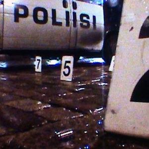 Poliisin asettamia numerokylttejä kadulla, taustalla poliisiauto.