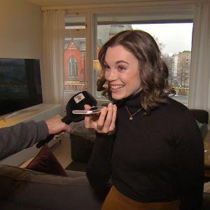 Sara Ray, en dam med svart lockigt hår och svart tröja, har en Yle-mikrofon och sin mobiltelefon framför sig där hon pratar med sin farmor.