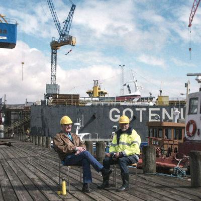 Två män sitter på stolar på en träkaj i en hamn med en kaffetermos.