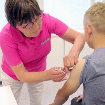 Terveydenhoitaja Mirja Salminen rokottaa 13-vuotiasta Niko Lukkalaa.