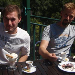 Kaksi viiksekästä miestä ravintolan terassilla nauttimassa jälkiruokia ja kahvia.
