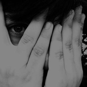 Person döljer ansikteti händerna och ett öga kikar mellan fingrarna.