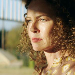 Karaktären Katrina står på en veranda med solen i ansiktet.