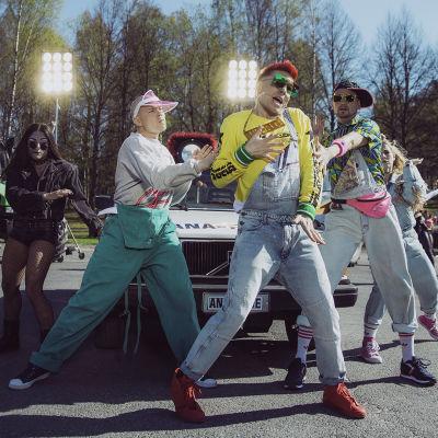 Tanssijat Antti Tuiskun Kesäkumibiisinvideon kuvauksissa koripallokentällä, taustalla auto ja traktori