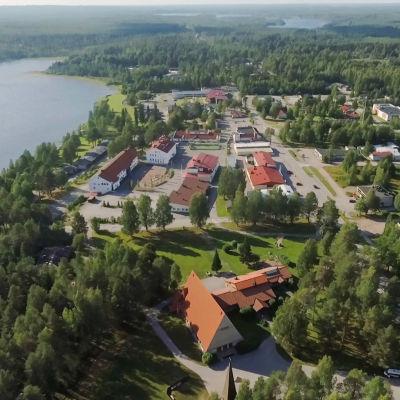 Pieni paikkakunta järven rannalla ja metsien ympäröimänä kesällä ilmasta kuvattuna.