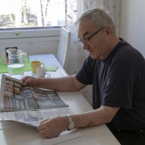 mies lukee Kalevaa keittiössä