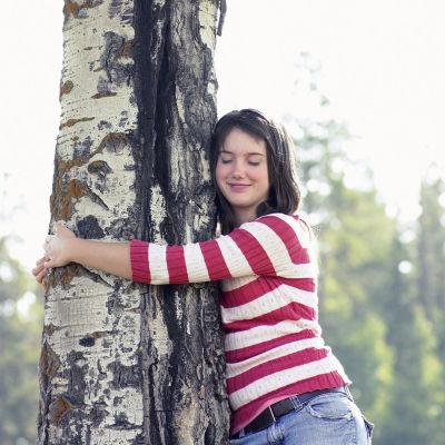 Nainen halaa puuta