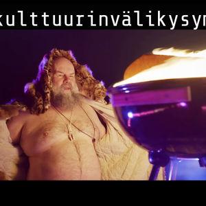 """Kari """"Tykylevits"""" Tykkyläinen seisoo turkki avattuna grillin ääressä #kulttuurivälikysymys -videon kuvauksissa"""