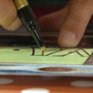 Närbild på textning med guldpenna.