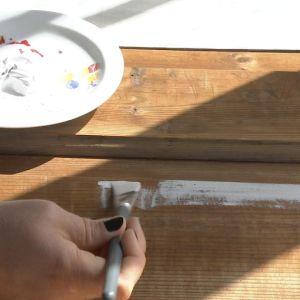 Målar med vit färg en gammal dörr