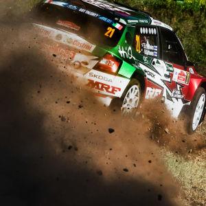En rallybil kör så fort att sanden flyger.