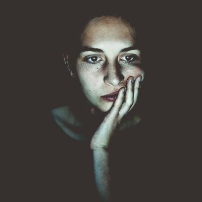 Naisen kasvot tietokonenäytön valossa.