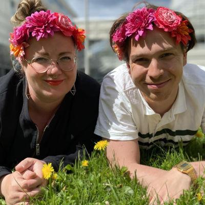 Programledarna för Hangö Teaterträff 2020 Kia Svaetichin och Tom Rejström ligger på gräsmattan med blommor i håret