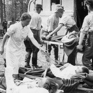 Haavoittuneita suomalaisia sotilaita hoidetaan sidontapaikalla.