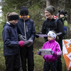 Helmi, Mikael, Heidi, Milo ja Minea Vanhala tutkivat karttojaan metsässä. Oikealla alakulmassa on rastilippu.