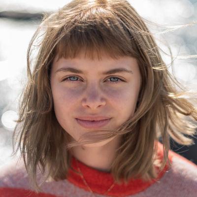 Nuori nainen lähikuvassa, taustalla meren kimallusta