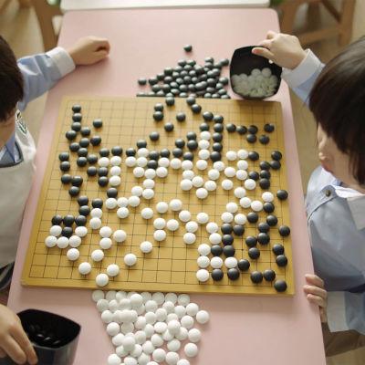 Två barn sitter och spelar go. Det kvadratiska brädet mellan dem är fullt med vita och svarta spelknappar.