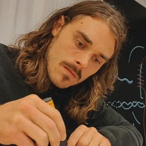 Oscar Hagen tecknar med en svart tusch