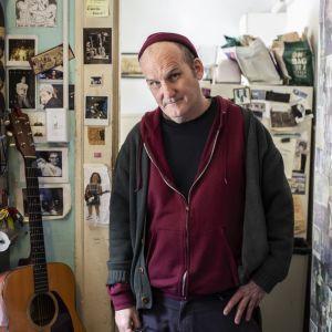 Yhdysvaltalainen muusikko Ian MacKaye Dischord House -nimisen talon oven suulla. Seinillä ja ovessa kymmeniä punk-bändien kuvia.