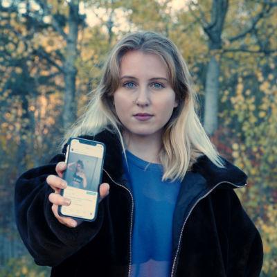 Vaaleahiuksinen nainen seisoo koivumetsän edessä ja näyttää puhelimen ruutua kameralle. Instagram on auki ruudulla.