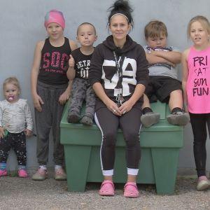 Äiti istuu viiden lapsensa kanssa roskalaatikon kannella