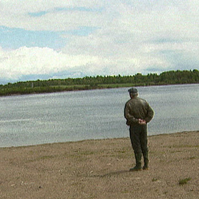 Jakaväkirykmentti 12 sotaveteraani katselee tunteikkaana järven rannalla yli veden. Selin kameraan.