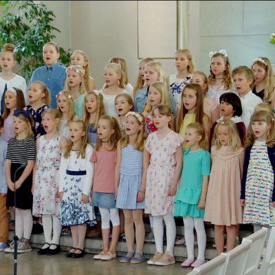 Pastellklädda barn med blommor i håret sjunger framme i en kyrka.